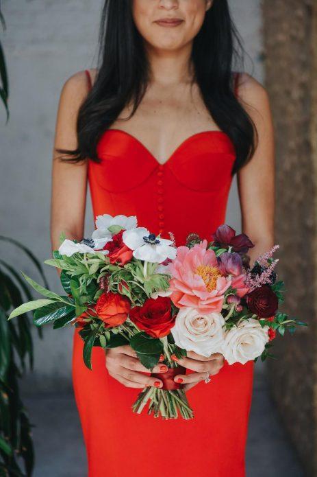 Невеста в красном платье с необычным букетом